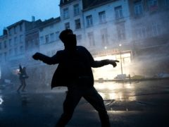 A protestor throws stones toward police officers in the Belgium capital, Brussels, Wednesday, Jan. 13, 2021, at the end of a protest asking for authorities to shed light on the circumstances surrounding the death of a 23-year-old Black man who was detained by police last week in Brussels. The demonstration in downtown Brussels was largely peaceful but was marred by incidents sparked by rioters who threw projectiles at police forces and set fires before it was dispersed. (AP Photo/Francisco Seco)