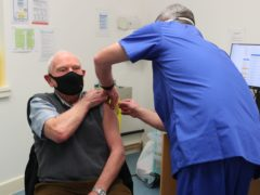 Pharmacist Andrew Hodgson administers a dose of the coronavirus vaccine to Robert Salt, 82, at Andrews Pharmacy in Macclesfield, Cheshire (Peter Byrne/PA)