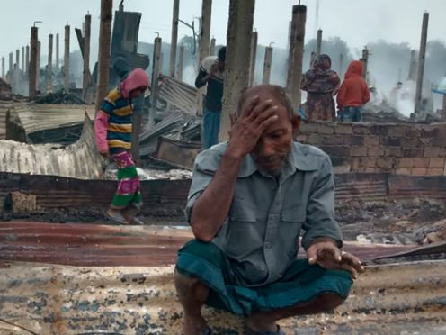 A Rohingya refugee sits by charred remains after a fire broke out in Nayapara Camp in Bangladesh (Mohammed Faisal/AP)