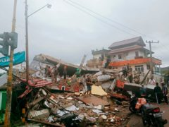 Residents inspect earthquake-damaged buildings in Mamuju, West Sulawesi, Indonesia, Friday, Jan. 15, 2021. A strong inland and shallow earthquake hit eastern Indonesia early Friday causing people to panic in parts of the country's Sulawesi island and run to higher ground. (AP Photo/Rudy Akdyaksyah)