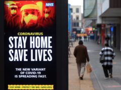 People pass a Stay Home, Save Lives electronic board in Leicester (Mike Egerton/PA)