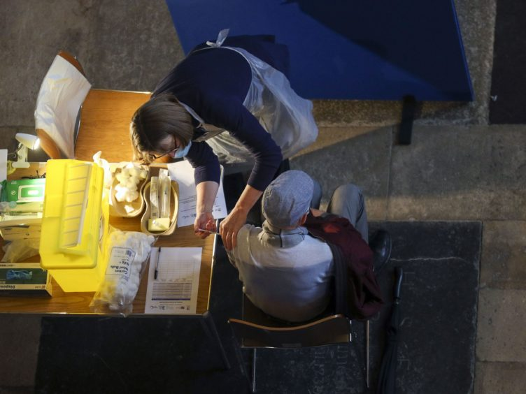 A man receives an injection of the Pfizer coronavirus vaccine at Salisbury Cathedral (Steve Parsons/PA)