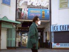 A man wearing a face mask passes a coronavirus information sign in Bournemouth (Steve Parsons/PA)