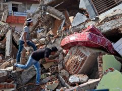 Residents inspect a building collapsed in Friday's earthquake in Mamuju, West Sulawesi, Indonesia (Yusuf Wahil/AP)