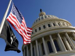 Flags fly on the US Capitol in Washington ahead of the 59th Presidential Inauguration (Susan Walsh/AP