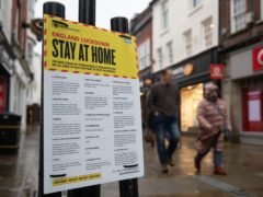 People walk past a Government sign warning people to stay at home on the High Street in Winchester (Andrew Matthews/PA)