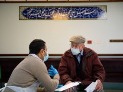 A member of the public is spoken to by a volunteer at the Al-Abbas Islamic Centre in Birmingham (Jacob King/PA)