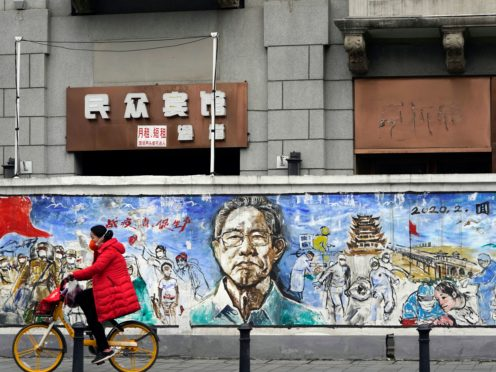 A resident rides past a mural titled 'Memories' in Wuhan, China, where coronavirus was first detected (Ng Han Guan/AP)