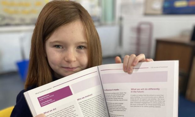 P6 pupil Keira Scott with the Education Scotland book.