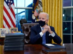 President Joe Biden waits to sign his first executive order in the Oval Office of the White House (AP/Evan Vucci)