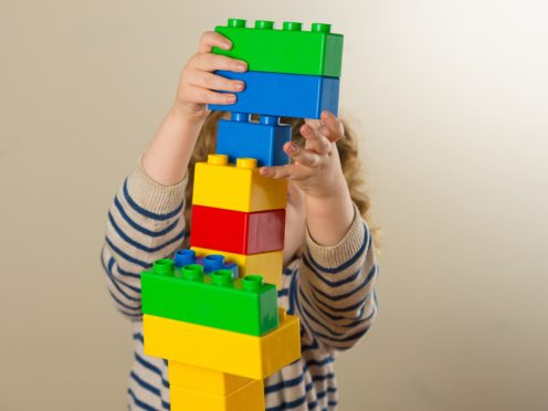A preschool age child plays with plastic building blocks (Dominic Lipinski/PA)