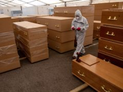A volunteer walks by coffins at Central Jamia Mosque Ghamkol Sharif in Birmingham in April 2020, which operated as a temporary morgue during the Covid-19 pandemic (Jacob King/PA)