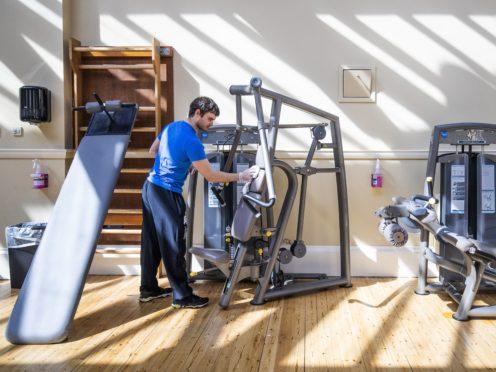 Martin Linden cleans gym equipment at the Arlington Baths Club, Glasgow (Jane Barlow/PA)