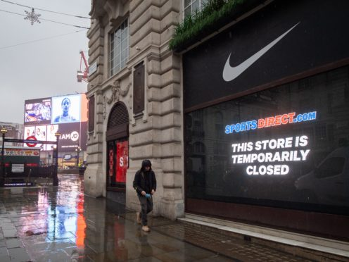 A man passes closed shops near Piccadilly Circus in London during England's third national lockdown (Dominic Lipinski/PA)