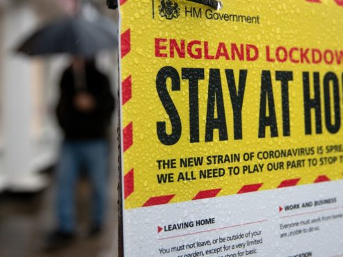 People walk past a Government sign warning people to stay at home (Andrew Matthews/PA)
