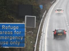 Vehicles make their way past a sign saying 'Refuge areas for emergency use only' on a smart motorway in Surrey (Andrew Matthews/PA)