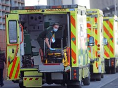 A paramedic wearing a face mask cleans the back of an ambulance at the Royal London Hospital in London (Yui Mok/PA)