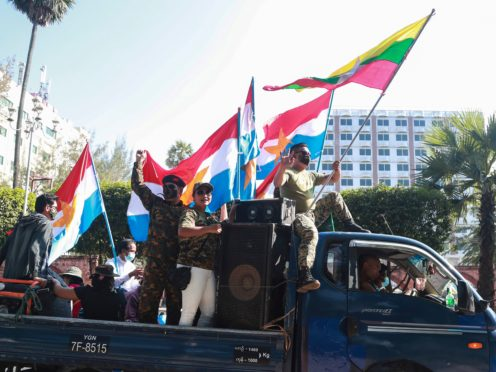 Supporters on a car wave national and military flags in Yangon a day after a coup which has once again shone a light on confusion over the use of the name Burma or Myanmar (Thein Zaw/AP)
