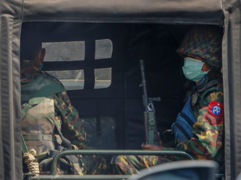Armed soldiers travel in a convoy of army vehicles patrolling in Mandalay in Myanmar on Wednesday (AP)