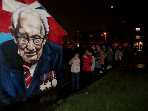 Local residents stand beside a mural of Captain Sir Tom Moore in Clonduff, east Belfast, as they join in with a nationwide clap (Brian Lawless/PA)