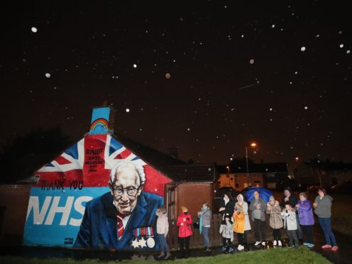 Local residents stand beside a mural of Captain Sir Tom Moore in Belfast as they join in with a nationwide clap in honour of the 100-year-old charity fundraiser (Brian Lawless/PA)