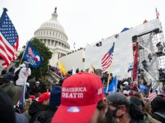 Insurrectionists loyal to President Donald Trump climb on an inauguration platform on the West Front of the US Capitol in Washington on January 6 (Jose Luis Magana/AP)