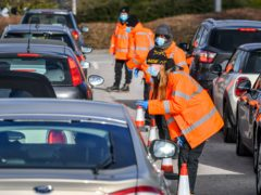 Testing staff hand out kits to motorists attending a Covid-19 surge testing centre at the Science Park, Emersons Green, in Bristol (Ben Birchall/PA)