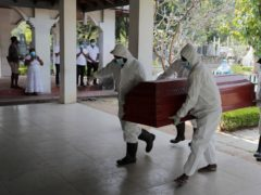 Sri Lankan health workers carry a coffin carrying remains of a Covid-19 victim to a cremation furnace (Eranga Jayawardena/AP)