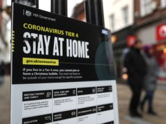 People make their way past a Government coronavirus Tier 4 sign (PA)