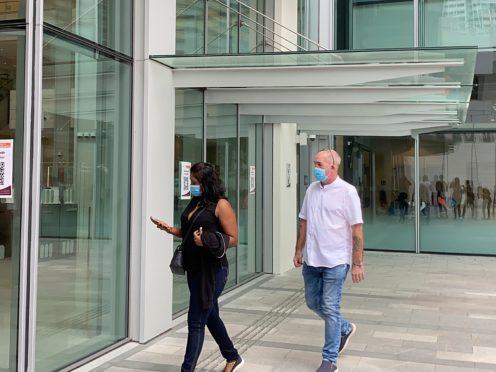 Agatha Maghesh Eyamalai and Nigel Skea walk into the State Courts in Singapore (AP)
