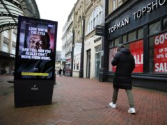 A person makes their way past a government coronavirus sign on Old Christchurch Road in Bournemouth (Andrew Matthews/PA)