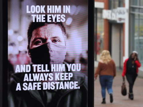 People make their way past a government coronavirus sign on Commercial road in Bournemouth, Dorset, during England's third national lockdown to curb the spread of coronavirus (Andrew Matthews/PA)