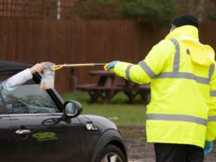 A coronavirus test is handed out of a car window in the car park of the Bramley Inn, Hampshire, during a surge testing programme for local residents (Andrew Matthews/PA)