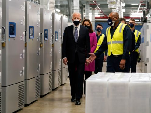 President Joe Biden walks past freezers used to store Pfizer's Covid-19 vaccine as he tours a Pfizer manufacturing site (AP)