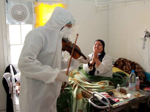 Dr Mohamed Salah Siala plays the violin for patients on the Covid wards of the Hedi Chaker hospital in Sfax, eastern Tunisia (AP)
