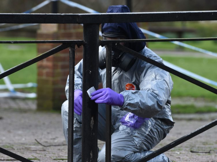 A scientist in a haz-mat suit takes samples (PA)