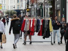 A man wheels a rack of clothing down a shopping street (Brian Lawless/PA)