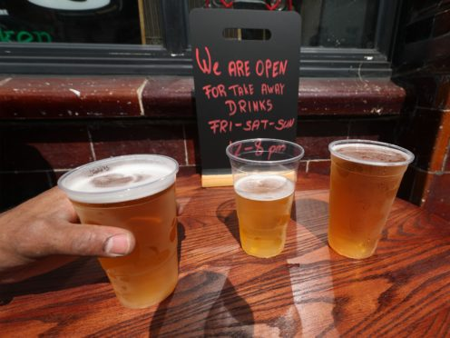 Takeaway pints of beer outside Charrington's Noted Ales And Stout pub in London (Yui Mok/PA)