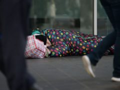 People walking past a homeless man in London. (Nick Ansell/PA)