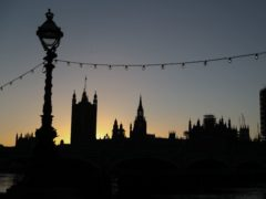 The sun sets behind the Houses of Parliament (Andrew Matthews/PA)