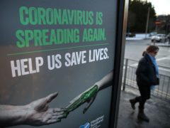 A person walks past a coronavirus-related poster (PA)