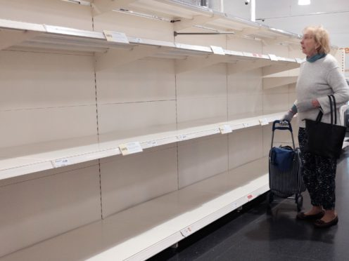 A shopper stares at empty shelves in a Sainsbury's store in London after people began panic buying due to the coronavirus pandemic (Yui Mok/PA)