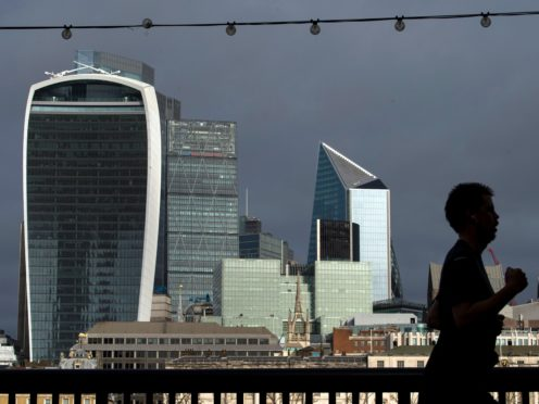 A person jogs along the riverside path past the City of London skyline (Kirsty O'Connor/PA)
