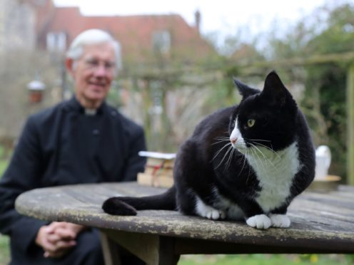 The Dean of Canterbury, the Very Reverend Dr Robert Willis with cathedral cat Lilly, one of three mischievous felines who live at the 1,400-year-old seat of worship in Kent, who keeps disrupting his video prayers and have become a social media hit. Picture date: Tuesday March 2, 2021.