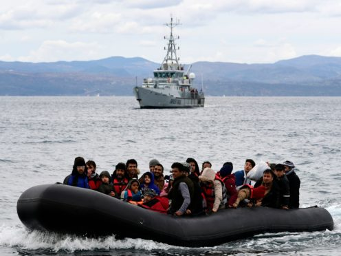 Migrants arrive aboard a dinghy accompanied by a Frontex vessel at the village of Skala Sikaminias, on the Greek island of Lesbos (Michael Varaklas/AP)