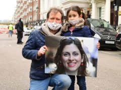 Richard Ratcliffe, the husband of Nazanin Zaghari-Ratcliffe, with his daughter Gabriella during a protest outside the Iranian Embassy in London (Ian West/PA)
