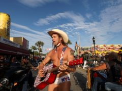 Robert Burck, better known as the Naked Cowboy, walks down the middle of Main Street while performing in Daytona, Florida (Sam Thomas/Orlando Sentinel via AP)