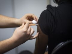 A woman receives an injection of the COVID-19 vaccine at the Science Museum in London, which has been opened as a Covid-19 vaccination centre. Picture date: Thursday March 11, 2021.