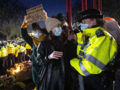 A woman talks to a police officer during a gathering in Clapham Common (Victoria Jones/PA)