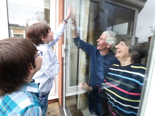 Ben and Isaac talk to their grandparents Sue and Alan through a window at their home in Knutsford, Cheshire (PA)